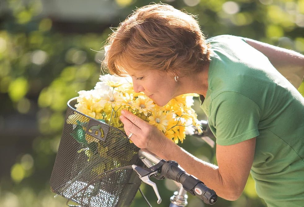 Jackie Bye Smelling Flowers in Bicycle Basket