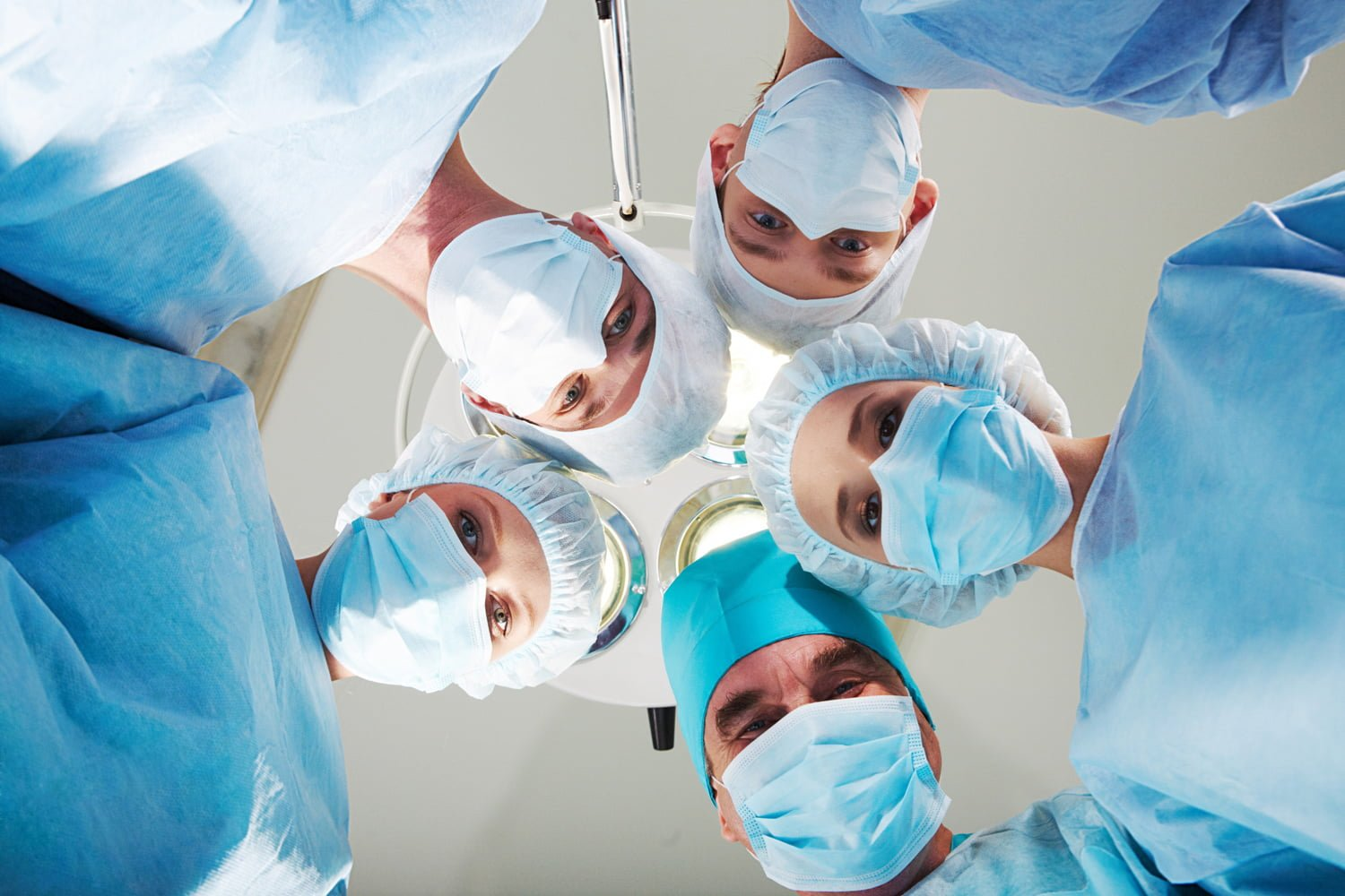 Surgeons Looking Down Upon Patient in Operating Room